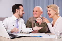 Old man and mature woman signing contract car lease. Old men and mature women signing contract car lease and hand over keys to manager stock photo