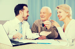Old man and mature woman signing contract car lease. Old men and mature women signing contract car lease and hand over keys to manager Royalty Free Stock Photos