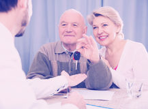 Old man and mature woman signing contract car lease. Old men and mature women signing contract car lease and hand over keys to manager Stock Image