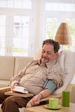 Old man measuring blood pressure at home Royalty Free Stock Photo