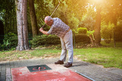 Old man at a minigolf court hits a ball with an iron racket. A w Stock Images