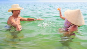 Old Man Mother Little Daughter Splash Water in Azure Sea. Bearded grandfather and mother play with little daughter in transparent azure sea stock video footage