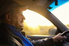 Old man with moustaches driving a car. Sun beams through a glass Stock Photos