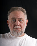 Old Man Mug Shot. An older man in a white t-shirt against black background with a scared or puzzled look as if in a mug shot Stock Images