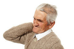 Old man with neck pain. Senior man with a strong pain in the back of his neck royalty free stock image