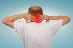Old man with neck spasm pain touching red inflamed area. Closeup senior mature man with bad neck spasm pain touching colored in red inflamed area suffering from Royalty Free Stock Photos