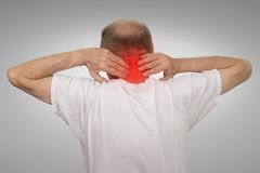 Old man with neck spasm pain touching red inflamed area. Closeup senior mature man with bad neck spasm pain touching colored in red inflamed area suffering from Stock Photography