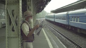 Old Man With Newspaper On Train Station. Attractive older man reading newspaper on train station stock video footage