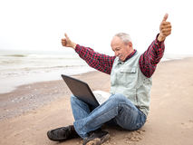 Old man with notebook on beach Stock Photos