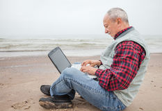 Old man with notebook on beach Royalty Free Stock Images
