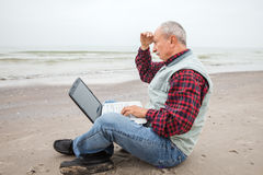Old man with notebook on beach Royalty Free Stock Photo