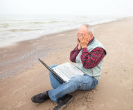 Old man with notebook on beach Stock Photography