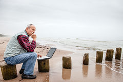 Old man with notebook on beach Royalty Free Stock Photos