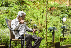 Old man at old age home. Sitting in a chair Royalty Free Stock Photography