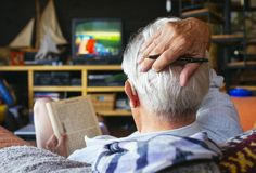 Old man. Watching television and puzzle Stock Photography