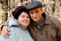 Old man and old woman in autumnal forest Stock Photos