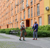 Old man and old woman dancing in the open air. Old men and old women dancing in the open air near the multi-colored apartment blocks Stock Image