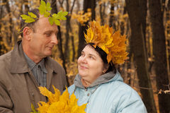 Old man and old woman with wreath of maple leaves Royalty Free Stock Images