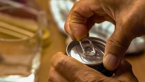 Old man open the lid of aluminum can of carbonated drink with fingers.