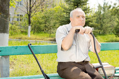 Old man outdoors. Portrait of old man sitting on the bench park waiting for someone Royalty Free Stock Images