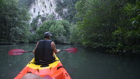 Old man paddles on kayak to cliff among jungle stock video footage