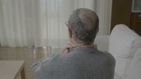 Old man in pain massaging his back neck having a muscle cramp or column spinal discomfort - stock footage