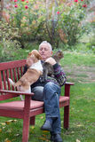 Old man with pets in the park. Senior man enjoying company of his dog and cat on the bench in the park Stock Image