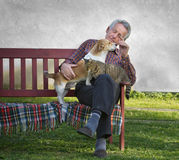 Old man with pets. Senior man with dog and cat on his lap on bench Royalty Free Stock Photo