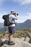 Old man photographer on mountain top Royalty Free Stock Photo
