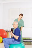 Old man in physical therapy praxis. Old men with dumbbells on gym ball in a physical therapy praxis Royalty Free Stock Image
