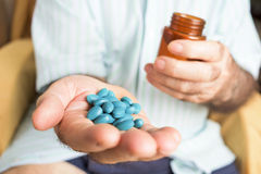 Old man with a pile of blue pills in his hand Royalty Free Stock Image