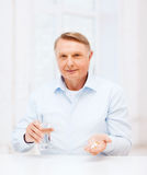 Old man with pills ang glass of water. Healthcare, madicine, pharmacy and elderly concept - old man with pills and glass of water Stock Image