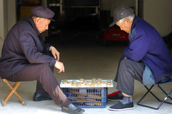 Old man play Chinese Chess. Two old Chinese man play Xiangqi near the door that opend to outside in storeroom Royalty Free Stock Photos