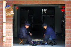 Old man play Chinese Chess. Two old Chinese man play Xiangqi near the door that opend to outside in storeroom Royalty Free Stock Photography