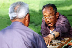 Old man play Chinese Chess. Two old Chinese man play Xiangqi in garden.Xiangqi, or Chinese Chess, is an extremely popular game in China Stock Photo