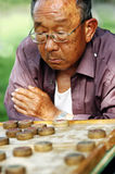 Old man play Chinese Chess. The old Chinese man play Xiangqi in garden.Xiangqi, or Chinese Chess, is an extremely popular game in China Royalty Free Stock Image