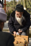 Old man play Chinese Chess. Two old Chinese man play Xiangqi  outside. Xiangqi, or Chinese Chess, is an extremely popular game in China Royalty Free Stock Photo