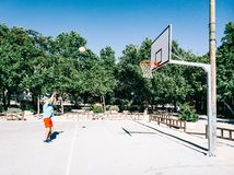 Old man playing in a court basket. Old man pland coaching basket alone in a basketball court stock photography