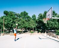 Old man playing in a basketball field. Old man pland coaching basket alone in a basketball court royalty free stock images