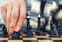 Old man playing chess. And make the first move Royalty Free Stock Images