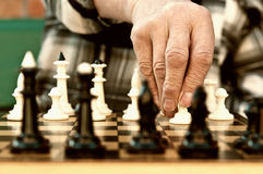 Old man playing chess. And make the first move Stock Photography