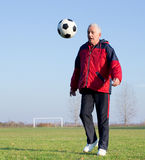 Old man playing football Stock Image