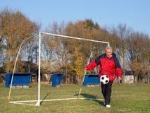 Old man playing football Stock Photos