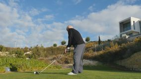 Old man playing golf. Senior man hits the ball with golf club. The male looks at the distance how far the ball flies. Elderly man spend his leisure time stock footage