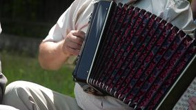 Old man playing music on the accordion stock footage