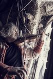 Old man playing music on a classical wooden violin. Retro toned image of a man with tousled long hair in old torn sweater full of holes playing music on a royalty free stock photos
