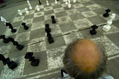 Old Man Playing Oversize Chess Stock Photography