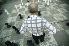 Old Man Playing Oversize Chess Board. Old man playing chess on an oversize concrete board, in the center of Salzburg City in Austria (Europe Stock Image