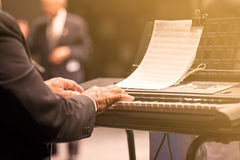 Old man playing piano Stock Photo