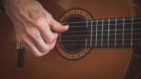 Old man plays guitar - picking hand Stock Images